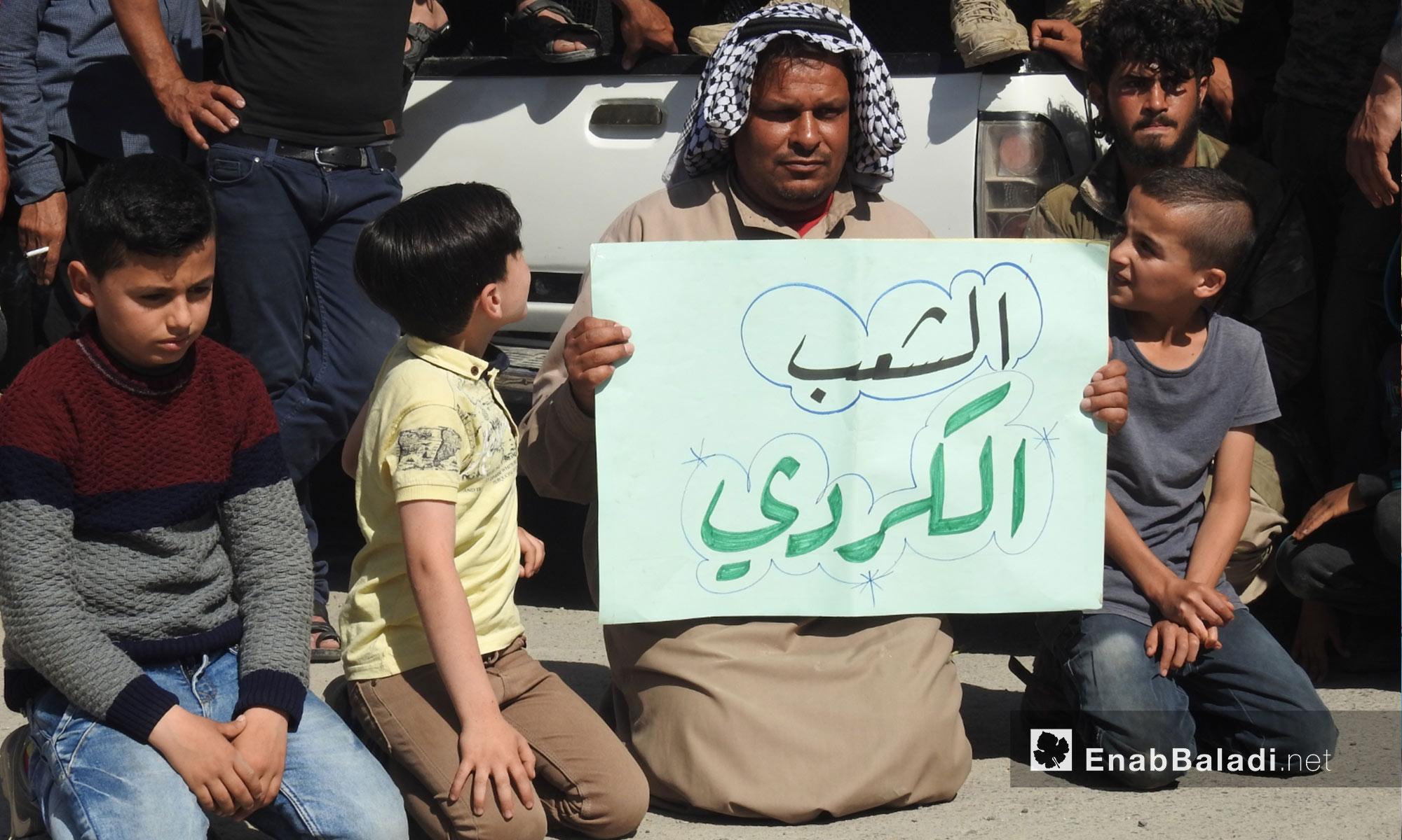 رجل يرفع لافتة خلال مظاهرات في جرابلس التحرك نحو شرق الفرات - 6 من نيسان 2018 (عنب بلدي)